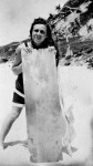 Could this be author Britt Melville, caught in a tidal time warp? Unidentified girl with a 'body board' for surfing, Snapper Rocks, Coolangatta, Queensland circa 1920 [picture] / Photographer unknown. Asset name LS-LSP-CD803-IMG0010