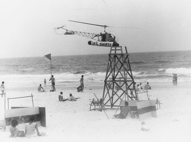 Photo: Beach 12 Helicopter hovering over Surfers Paradise beach for a publicity stunt, Surfers Paradise, Queensland, 1957 [picture]/ Alexander McRobbie, photographer. Asset name LS-LSP-CD908-IMG0001